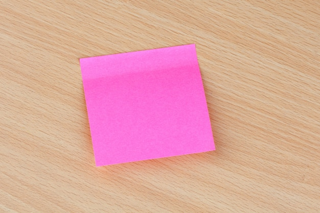 Pink post-it bloccato su una superficie di legno