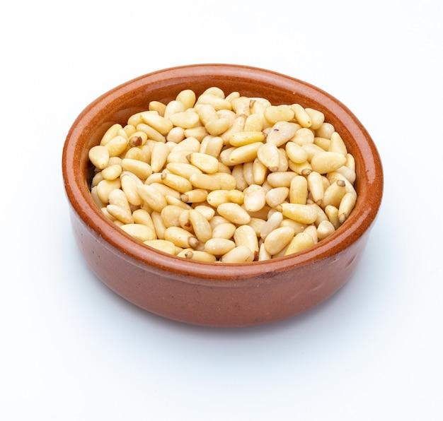 Pinoli in ciotola dell'argilla (raccolta di vari dadi). isolato