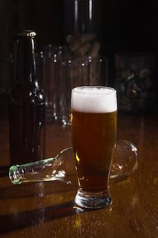 Pinta ad alto angolo con birra schiuma sul tavolo