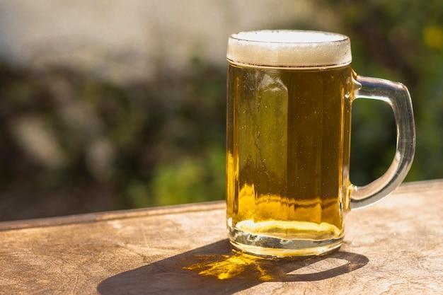Pinta di vista laterale con birra schiumosa sul tavolo