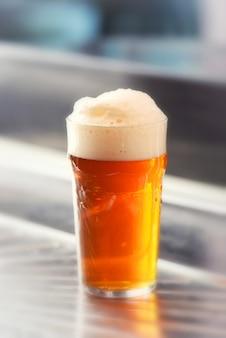 Pinta fresca servita di birra alla spina schiumosa in un bicchiere