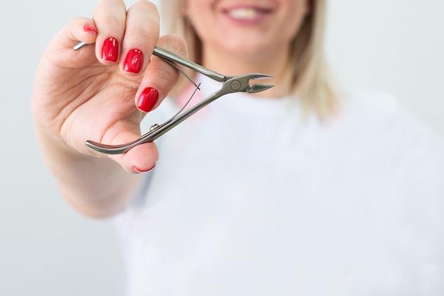 Pinza per cuticole. le mani tengono uno strumento per manicure e pedicure. copia spazio. concetto di industria di bellezza