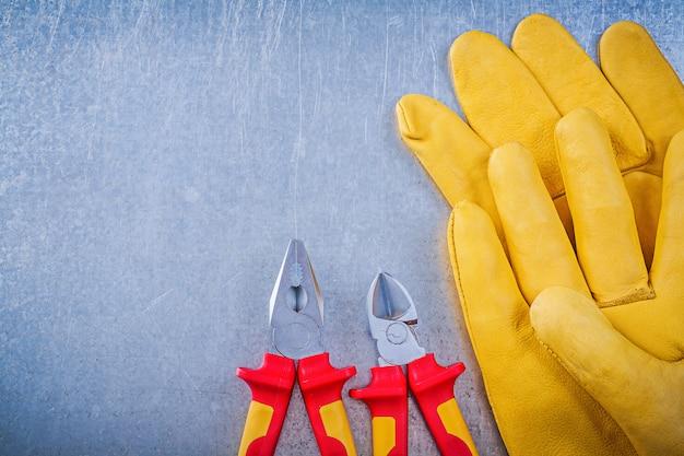 Pinze di cuoio delle pinze dei guanti di sicurezza sul concetto metallico di elettricità della tavola