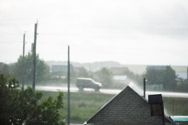 Pioggia sfocato da casa di campagna, albero, pilastri e auto in autostrada. concentrandosi sulla pioggia. tempo piovoso fuori città.