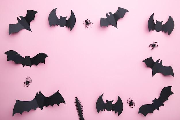 Pipistrelli di carta di halloween con ragni su sfondo rosa pastello. halloween