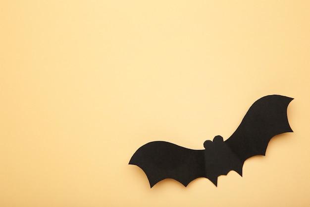 Pipistrello di carta di halloween su sfondo biege. concetto di halloween.