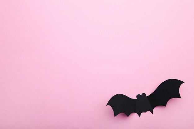 Pipistrello di carta di halloween su sfondo rosa pastello.