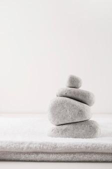 Piramide delle pietre sopra pulito asciugamano piegato isolato su sfondo bianco