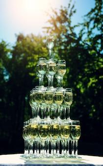 Piramide di bicchieri di champagne si trova sul tavolo all'aperto