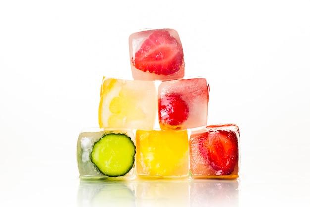 Piramide di cubetti di ghiaccio con frutti su una superficie bianca brillante. il concetto di estate calda, dessert, gelato. vista piana, vista dall'alto