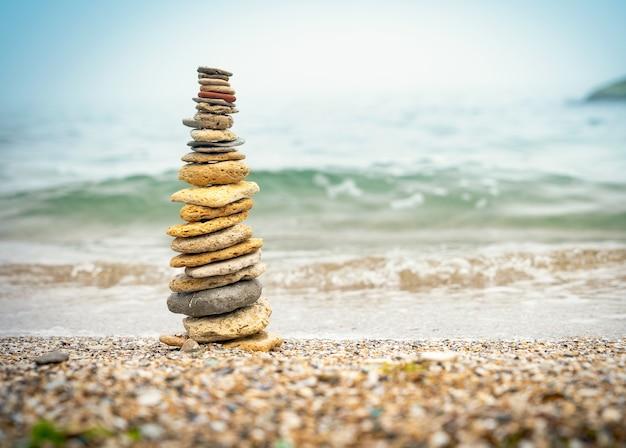 Piramide di pietre sulla sabbia che simboleggia zen, armonia, equilibrio. energia positiva. oceano sullo sfondo