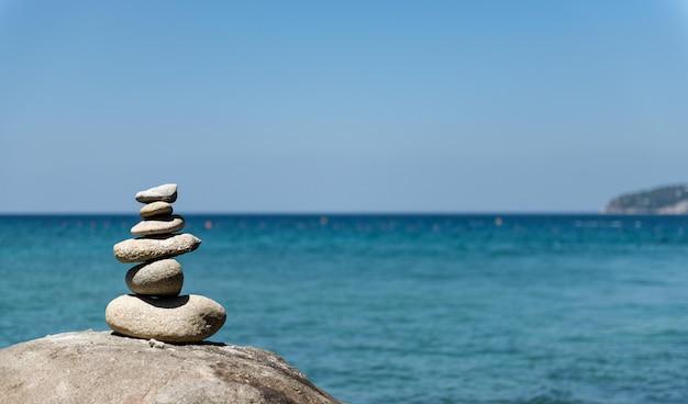 Piramide di pietre sulla spiaggia di ciottoli che simboleggia la stabilità, lo zen, l'armonia, l'equilibrio.
