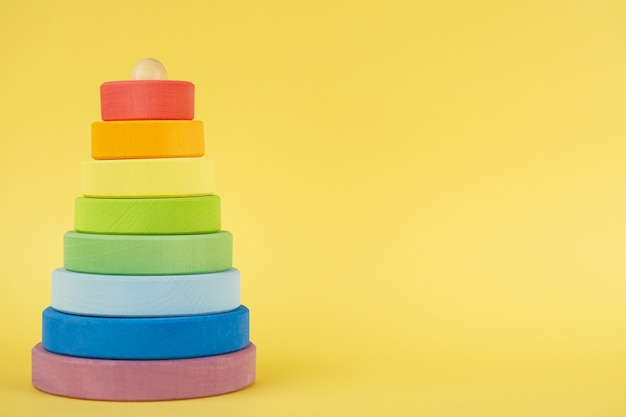 Piramide multicolore del bambino con lo spazio della copia su fondo giallo