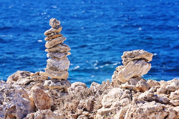 Piramide zen di pietre grezze sul mare sfocato