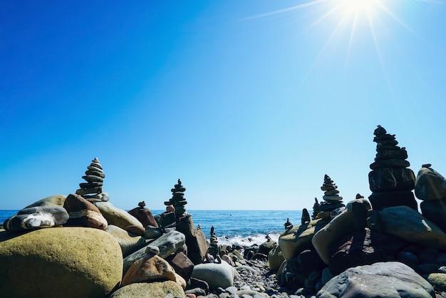 Piramidi di pietre sulla spiaggia con il sole splendente. crimea.