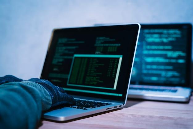 Pirata informatico che scrive sul computer portatile