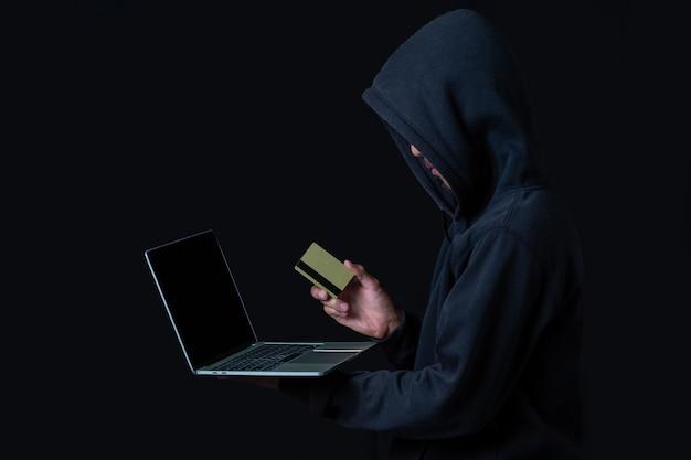 Pirata informatico con un computer portatile e una carta di credito dorata