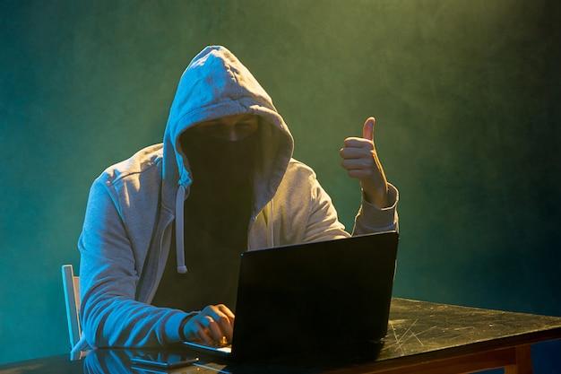 Pirata informatico di computer incappucciato che ruba informazioni con il computer portatile
