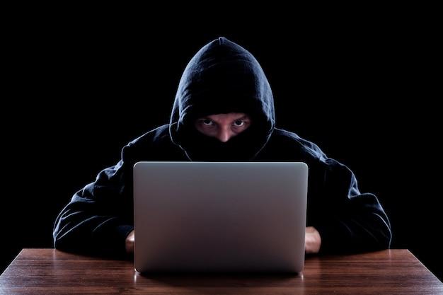 Pirata informatico di computer incappucciato che ruba informazioni