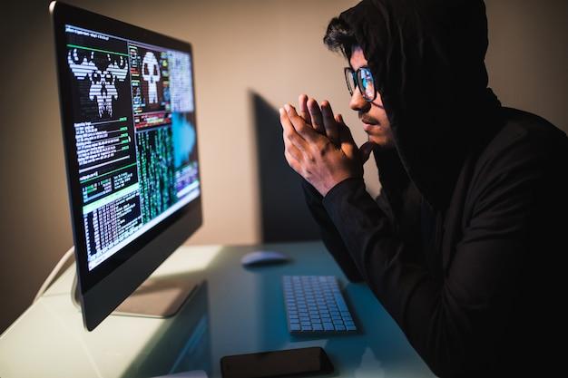 Pirata informatico di indianmale con lo smartphone e codifica sullo schermo di computer nella stanza scura