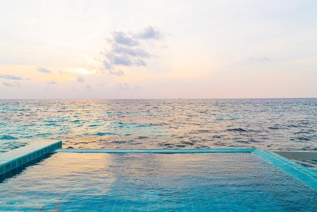 Piscina all'aperto con mare oceano e cielo al tramonto