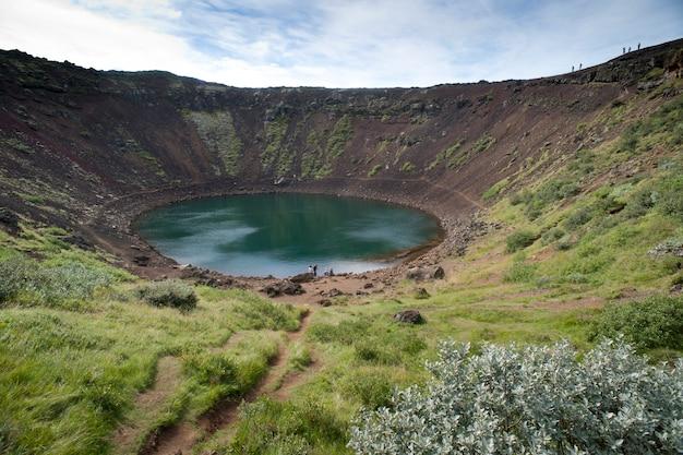 Piscina circolare di acqua in un cratere vulcanico con vegetazione verde circostante