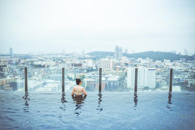Piscina sulla cima del tetto con la bella vista della città, vista della città di vista sul mare, pattaya, tailandia