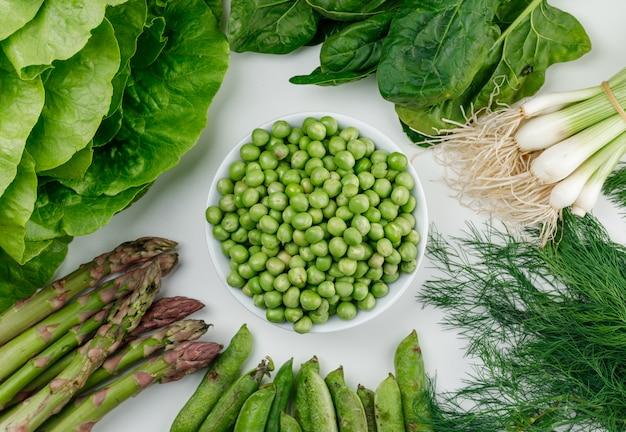 Piselli con lattuga, asparagi, baccelli verdi e cipolla, aneto, acetosa in una ciotola bianca sulla parete bianca, vista dall'alto.