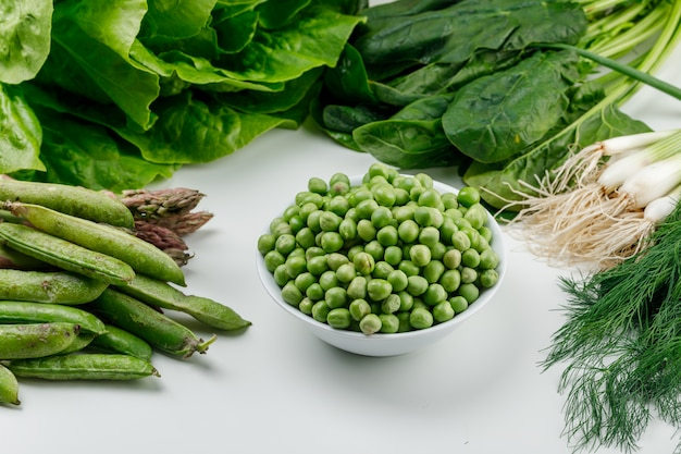 Piselli in una ciotola con baccelli verdi, acetosa, aneto, lattuga, asparagi, cipolle verdi vista dall'alto su un muro bianco