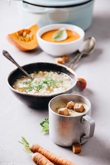 Piselli, pomodoro, minestre di verdure ed ingredienti su fondo concreto