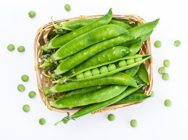 Piselli verdi, teneri, freschi e crudi. nel cestino di vimini