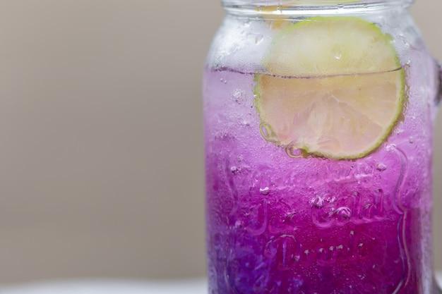 Pisello di farfalla porpora fresca o fiore del pisello blu e succo di limone in vetro con fondo verde della sfuocatura