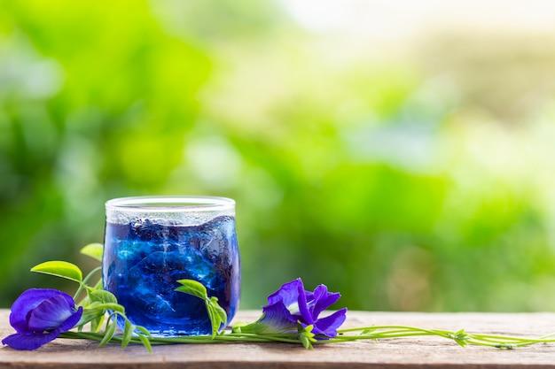 Pisello di farfalla porpora fresco o fiore e succo del pisello blu in vetro sul fondo di legno della tavola
