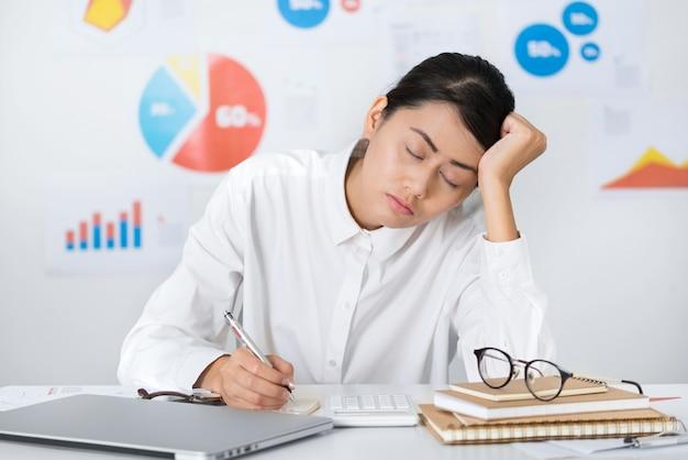 Pisolino asiatico della donna di affari mentre lavoro - concetti di finanza e di affari.