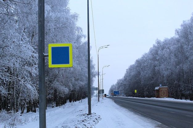Pista asfaltata in inverno con alberi innevati.