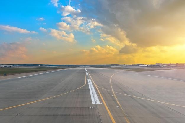 Pista dell'aeroporto nei cumuli di colore giallo di pendenza di azzurro del cielo della luce del sole di tramonto.