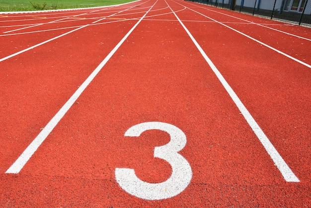 Pista di corsa con numero 3. sfondo colorato per lo sport.