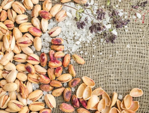 Pistacchi in guscio e pistacchi pelati con grandi cristalli di sale ed erbe aromatiche secche su sfondo di tela