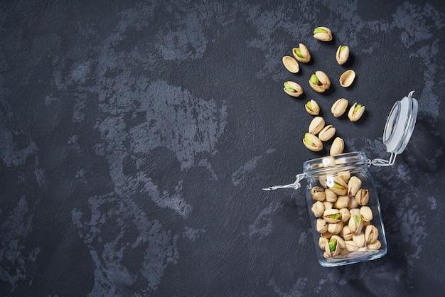 Pistacchi in un barattolo di vetro aperto sulla tavola nera, con copyspace. vista dall'alto.