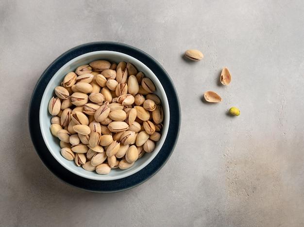 Pistacchi in una ciotola blu su una parete beige grigia. cibo salutare