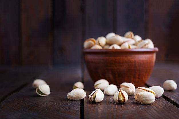 Pistacchi sul tavolo di legno. pistacchi salati arrostiti.