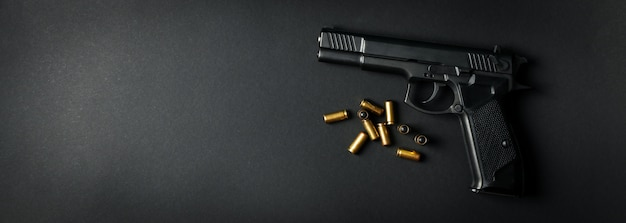 Pistola e proiettili traumatici sul nero. arma di autodifesa