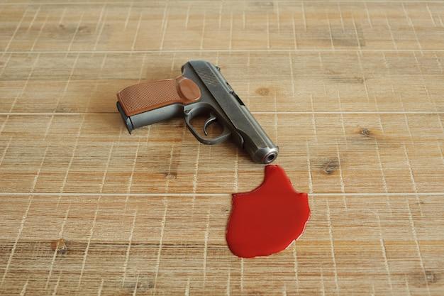 Pistola e sangue scarlatto su tavola di legno.