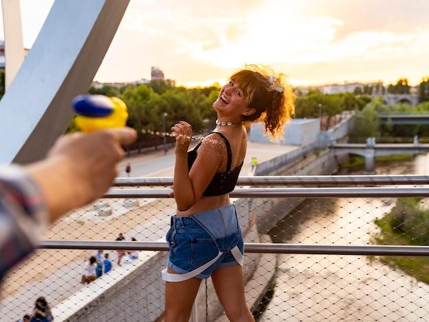 Pistole ad acqua persone che giocano e si divertono in una calda giornata estiva.