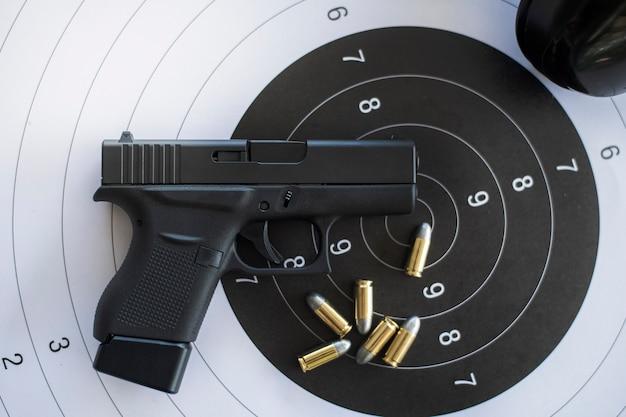 Pistole con munizioni sul bersaglio di carta