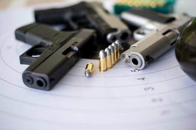 Pistole con munizioni sulla pratica di tiro al bersaglio di carta