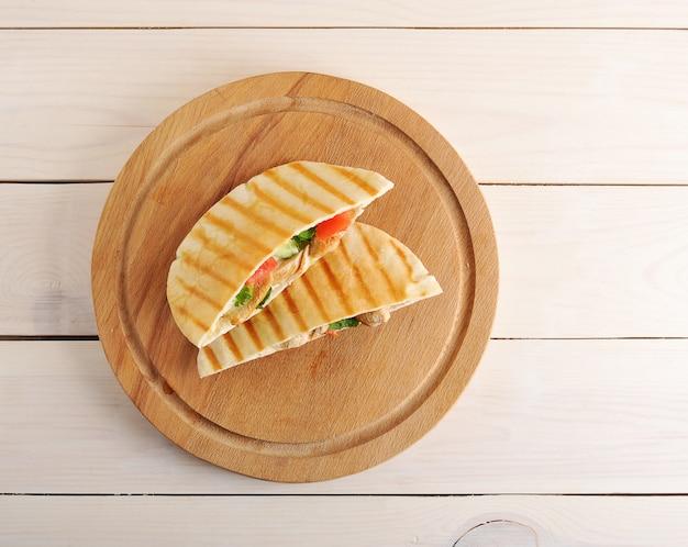Pita di focaccia ripiena di petto di pollo, verdure e salsa