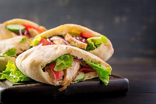 Pita ripiena di pollo, pomodoro e lattuga su cucina in legno, mediorientale.