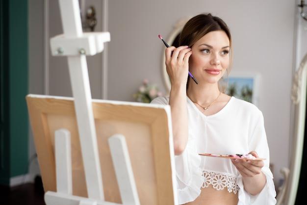 Pittore che disegna nello studio di arte facendo uso del cavalletto. ritratto di una pittura della giovane donna con le pitture ad olio su tela bianca, ritratto di vista laterale