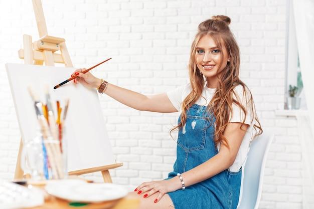 Pittore femminile abbastanza talentuoso che dipinge su cavalletto